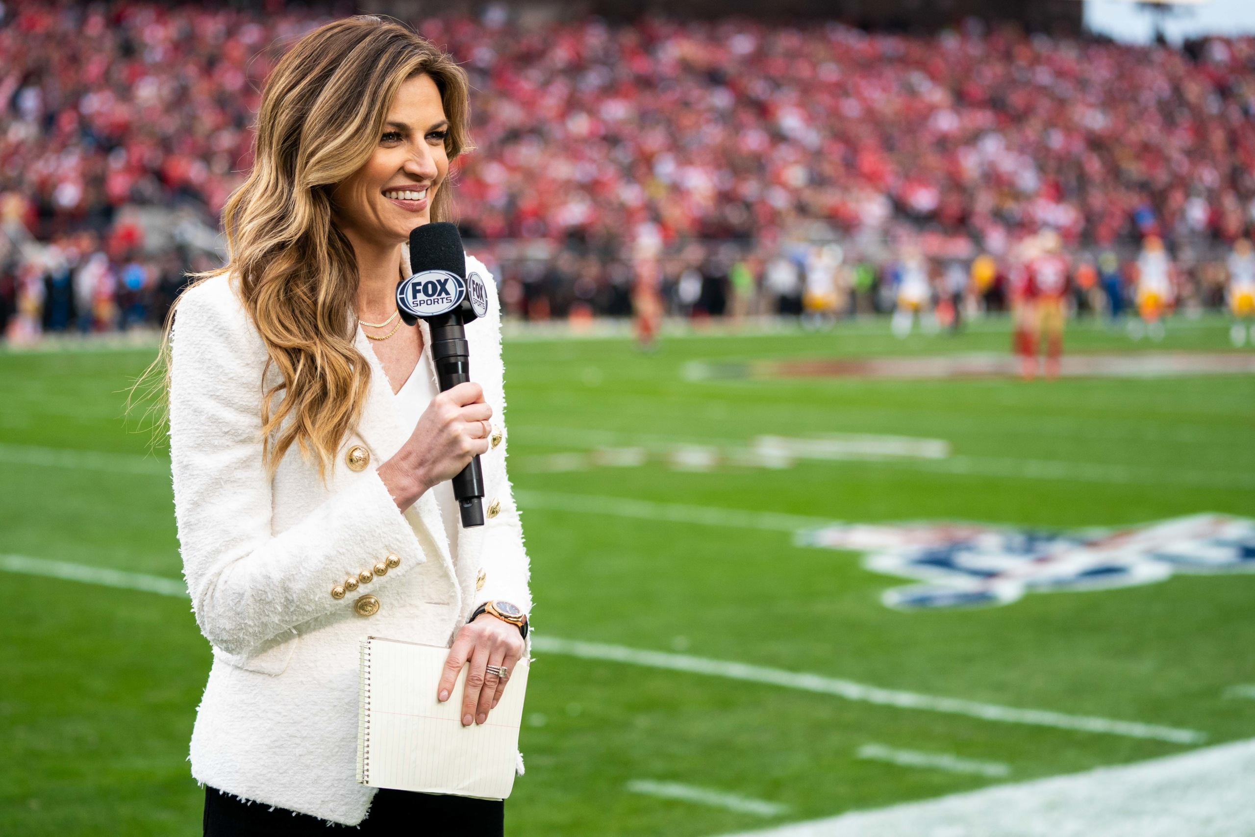 A sideline reporter films a hit at an NFL game.