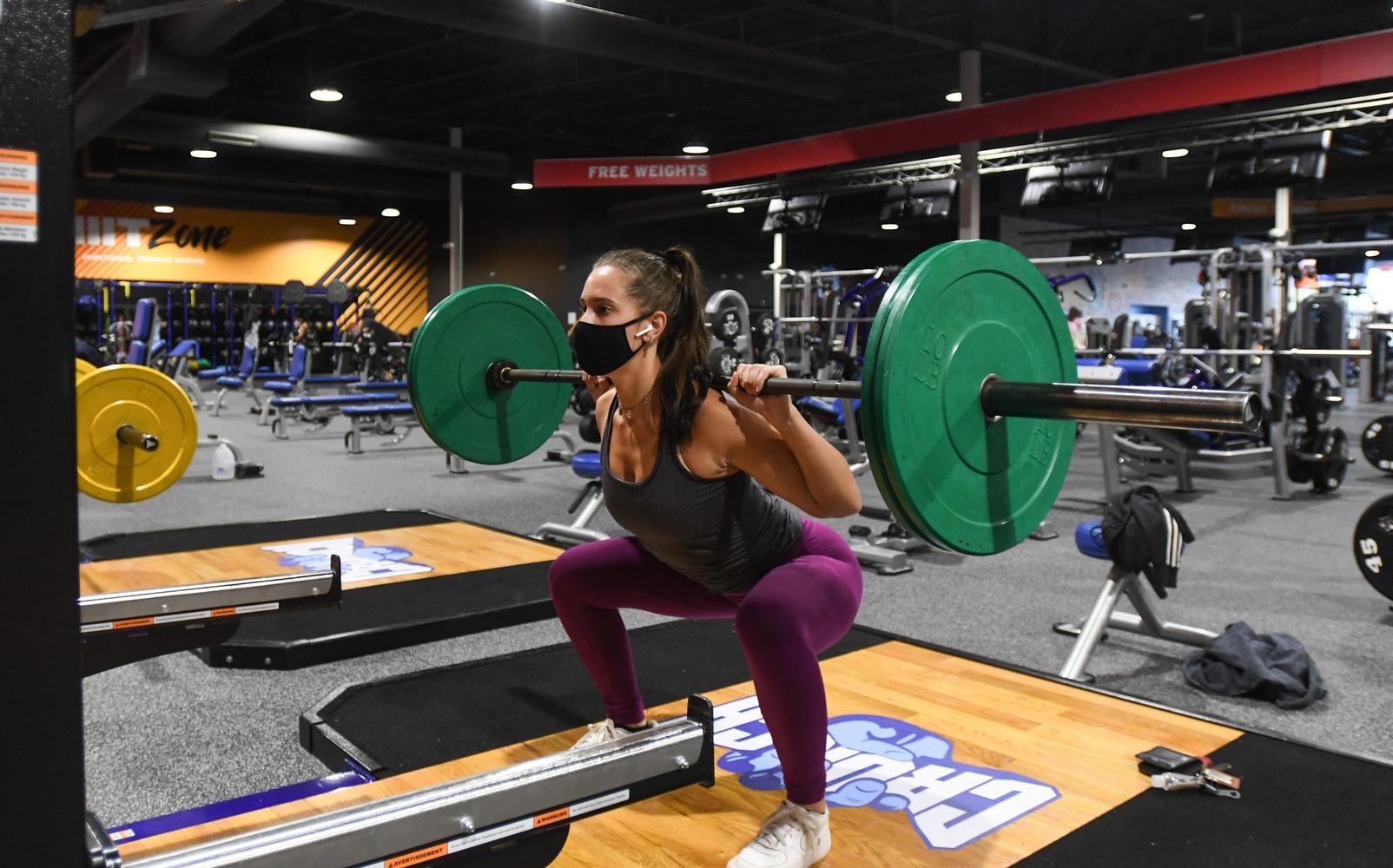 A woman squats at a gym